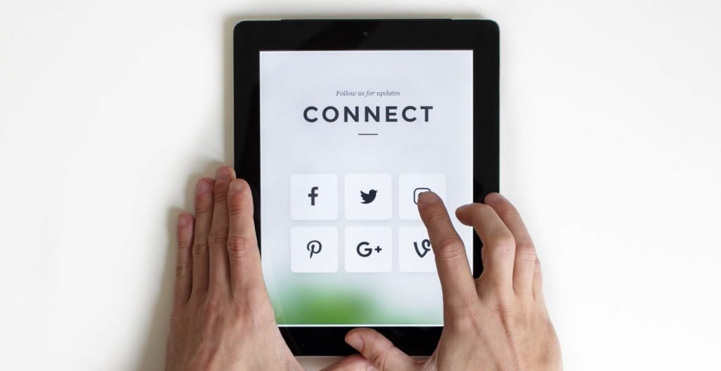 Tablet with social media buttons being pressed by a person's hand