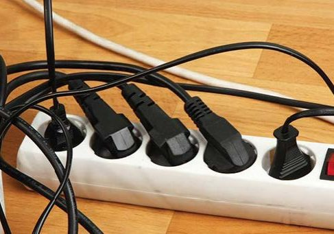 Power bar with multiple messy cords plugged in
