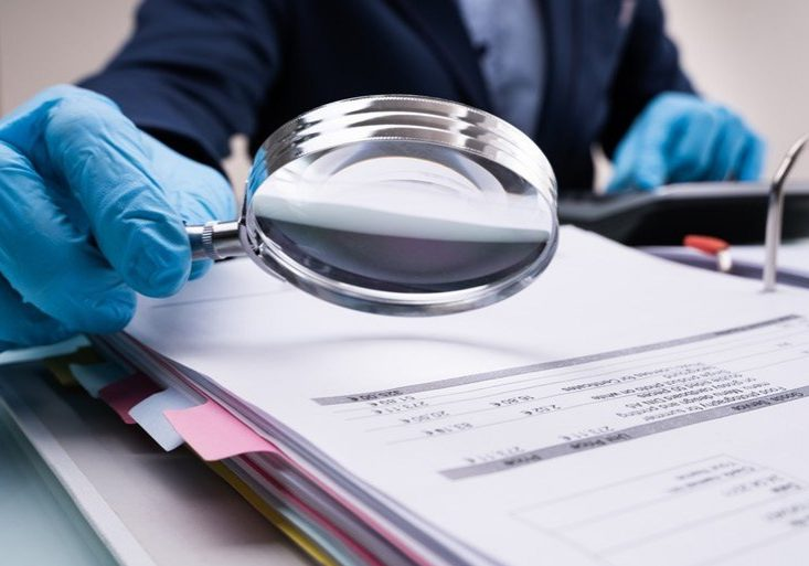 Magnifying glass inspecting business paperwork