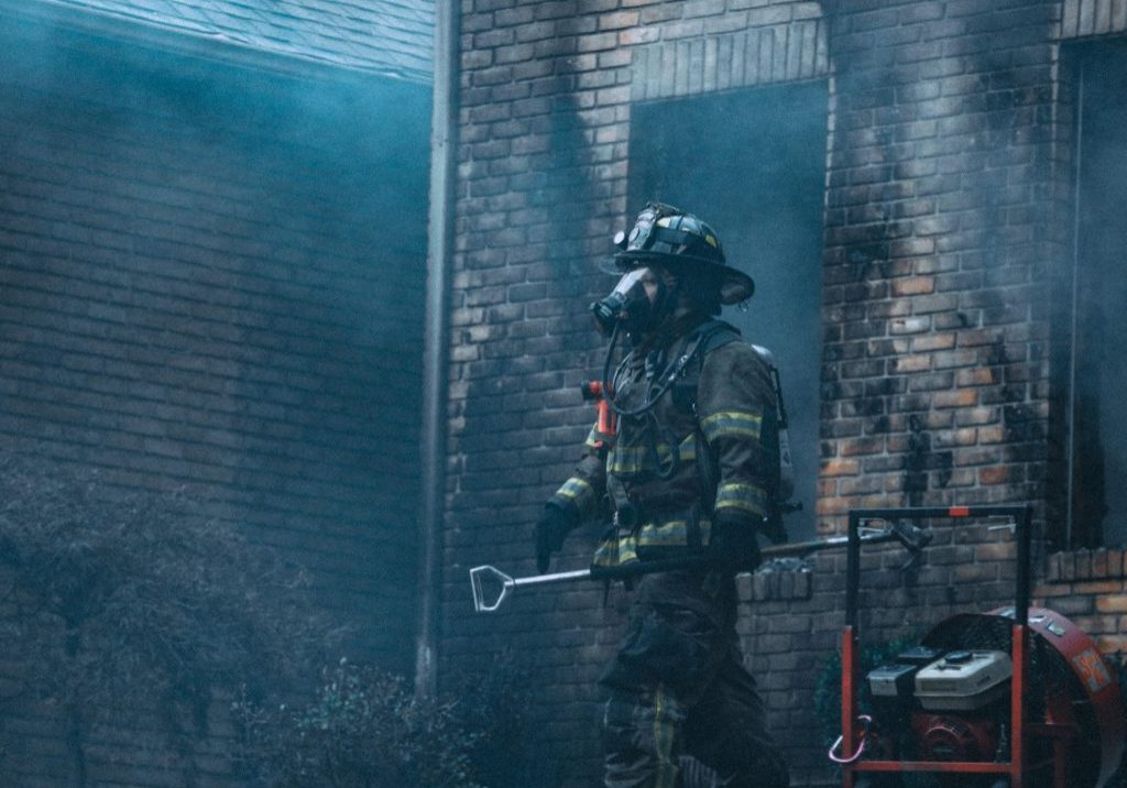 Firefighter exiting a burned building