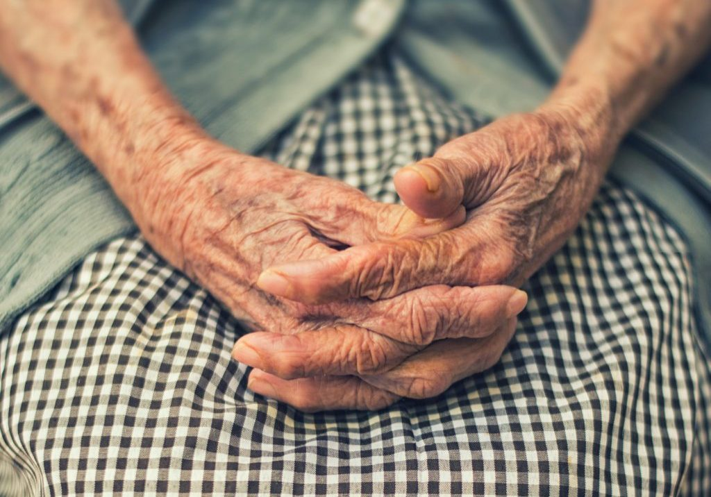 Older person's hands on their lap
