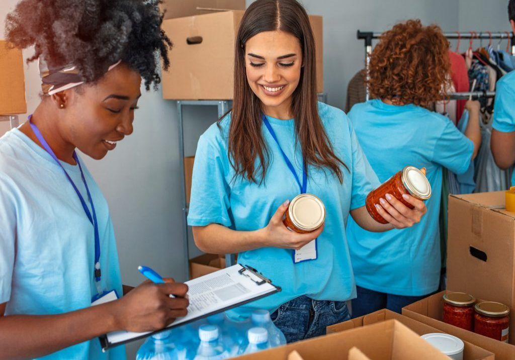 Volunteers sorting canned goods with a clipboard